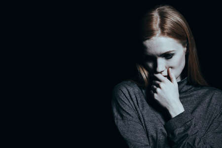 Portrait of a young, pale, sad girl standing against empty, black wall. Emotional breakdown concept. Standard-Bild