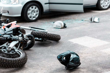 Overturned motorcycle and helmet on the street after collision with a car