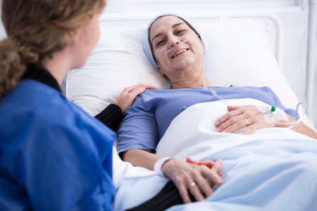 Smiling sick woman enjoying a visit of her caregiver supporting her during chemotherapy Standard-Bild