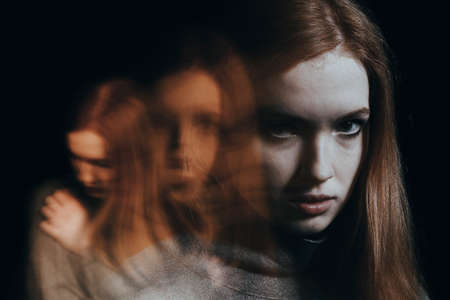 Blurred figures of a red-haired girl. Concept of mental illness