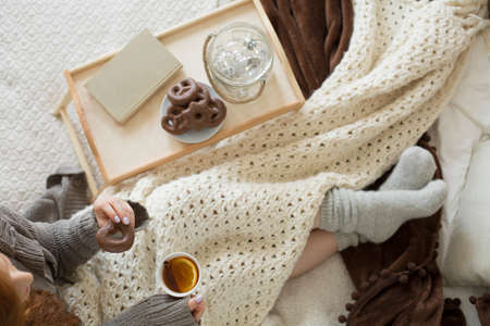 High angle of woman drinking tea with lemon while lying in bed with pretzels on wooden tray Standard-Bild