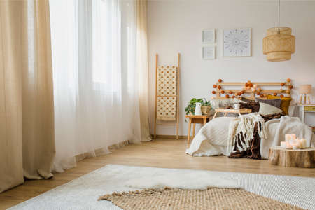 Candles on wooden stump next to bed with knit blanket in hygge style bedroom interior with brown curtain and posters