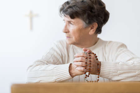 Senior woman praying with a rosary in a bright catholic church 스톡 콘텐츠