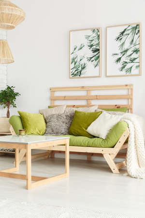 Side angle of wooden sofa with pear green futon, pillows and beige blanket in natural living room interior