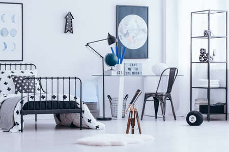 Black chair at desk with globe against the wall with moon poster in bright kids bedroom interior with telescope Standard-Bild