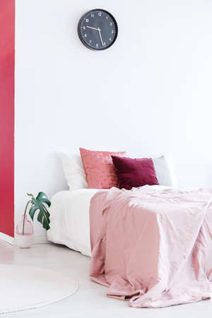 Pastel pink bedsheets on bed with cushions against white wall with black clock in bedroom interior Standard-Bild