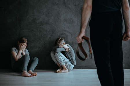 Angry parent with belt and crying siblings. Children as a victim of domestic violence concept 免版税图像