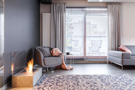 Patterned carpet and grey armchair with pink blanket near fireplace in contemporary apartment interior