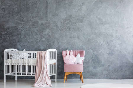 Modern baby room interior with white crib and pink armchair against grey, empty wall