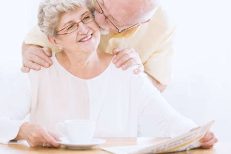 Happy elderly woman reading newspaper and her husband kissing her cheek