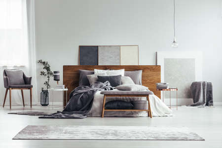 Grey and white bedroom interior with armchair, carpet, bed and painting standing on the floor Stockfoto