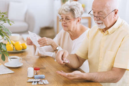 Senior man taking medication for diabetes while his wife reading a prescription Stockfoto