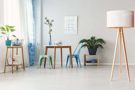 Wooden lamp in bright dining room interior with mint and blue chair at table next to a palm on stool against white wall with a poster