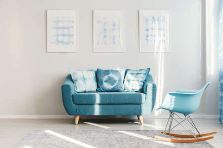Blauer Schaukelstuhl auf grauem Teppich und Türkis Couch mit gemusterten Kissen gegen weiße Wand mit Architekturen im minimalistischen Innenraum Standard-Bild - 95520094