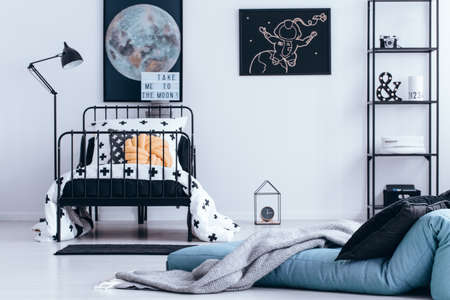 Blanket on blue mattress next to bed with pastel pillow in teenagers bedroom interior with moon and astronaut poster