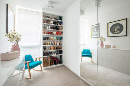 Womans shoes on shelves in cozy dressing room interior with blue armchair and mirror Standard-Bild