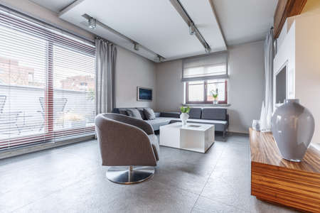 Grey armchair next to white table in modern living room interior with vase on cupboard and windows Standard-Bild