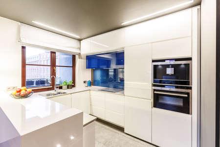 Brown window in white, modern kitchen interior with cabinets, oven and blue glaze Standard-Bild