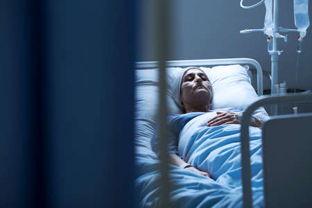 Lonely woman suffering from cancer while lying in a hospital bed