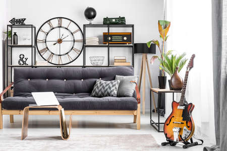 Laptop on wooden table and guitar in guys room interior with black sofa and round clock on the wall next to lamp