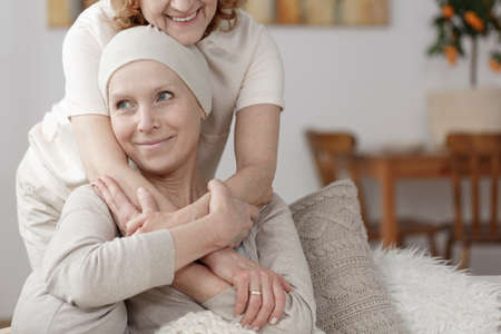 Family member supporting sick woman during chemotherapy treatment