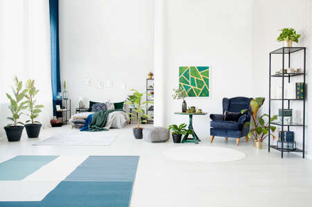 Patterned carpet and green painting in bright open space interior with bed and blue armchair next to table
