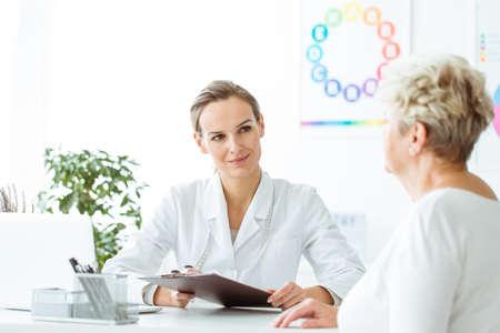Dietista sonriente tomando el historial médico del paciente durante una visita a la oficina