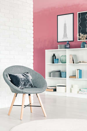 Pink Lamp On Cabinet Next To Grey Armchair In Modern Living Room ...