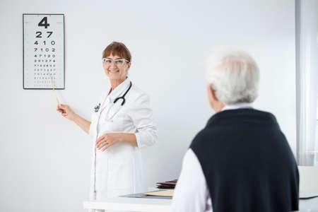 Smiling oculist doing an eye exam with her elder patient Stock fotó
