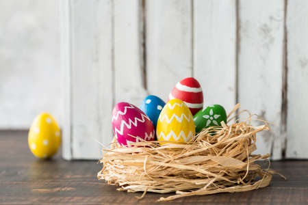 Colorful eggs in a nest as easter decoration against grey planks