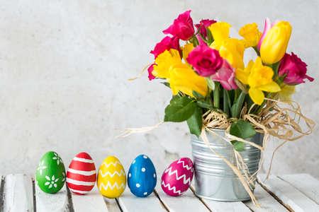 イースターエッグの隣にカラフルな花を持つ金属の植木鉢
