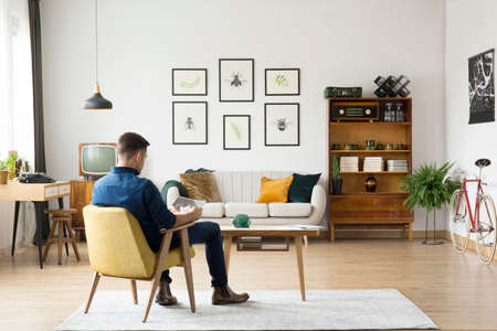 Man sitting in yellow chair at wooden table in retro living room interior with sideboard and gallery above a settee Stock Photo