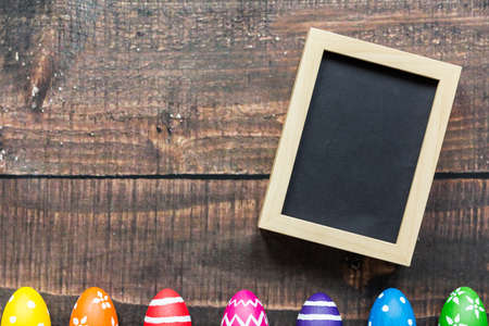 Black picture in wooden frame and colorful easter eggs Stock Photo