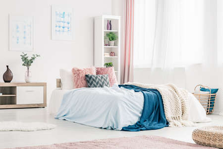 Pink pillows and blue blanket on bed in womanly bedroom interior with plant on wooden cupboard