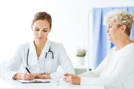 General doctor with stethoscope writing a prescription for a woman with a cold