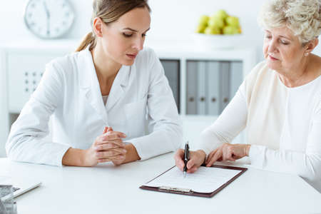Patient filling in a medical questionnaire during a visit to a family doctor
