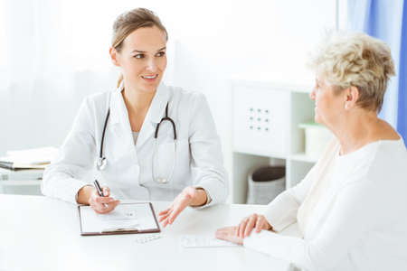 Smiling doctor with stethoscope and sick woman during dietician consultation Stock Photo