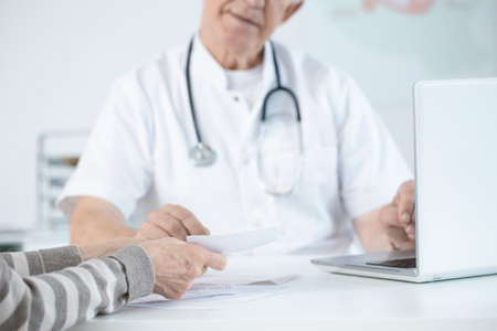 Close-up of elder doctor giving medical suggestions to his patient in an office Stock Photo