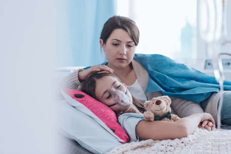 Worried mother taking care of a kid with cystic fibrosis lying in hospital bed with plush toy