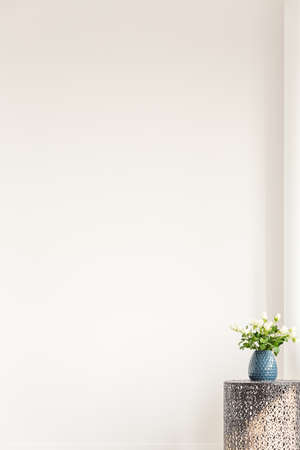 White flowers in blue vase on metal table against the wall with copy space in empty interior Stock Photo