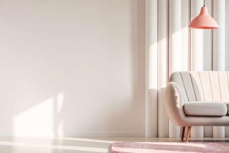 Lámpara de melocotón encima del sofá beige y alfombra rosa contra tubos de plástico en el interior de la sala de estar simple con espacio de copia en la pared blanca Foto de archivo