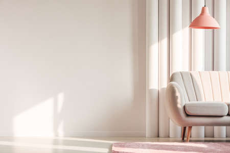 Peach lamp above beige couch and pink rug against plastic tubes in simple living room interior with copy space on white wall