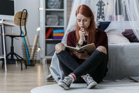 Redhead girl thinking over a notebook while sitting on a floor in her room Stock Photo