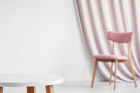 White wooden round table in the foreground against the wall with copy space and pink chair in the background in bright living room interior