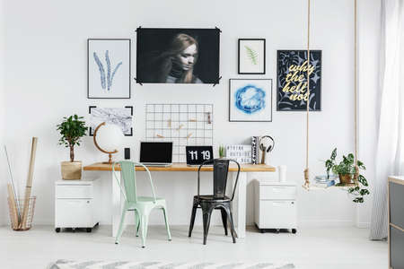Mint and black chair at wooden table in workspace interior with plant on cabinet and posters gallery on the wall