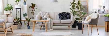 Fur on armchair in floral living room interior with wooden table next to sofa with knot pillow