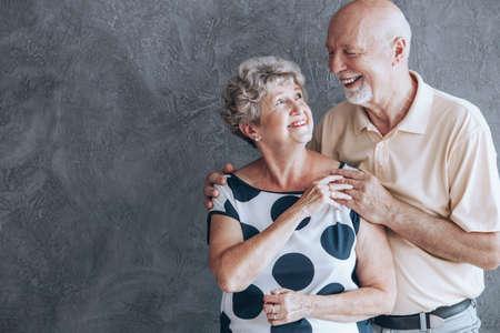 Een paar senioren vieren hun trouwdag en kijken elkaar liefdevol in de ogen