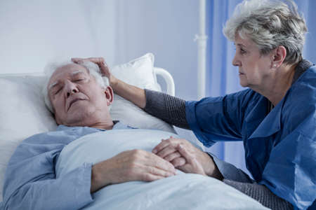 Caring wife comforting her elderly husband suffering from cancer