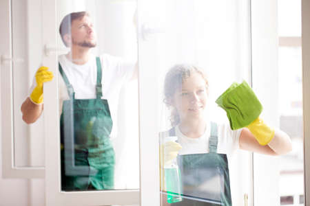 Professional cleaners with yellow gloves cleaning windows at a home Zdjęcie Seryjne - 96096409