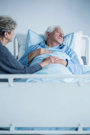 Weak senior man lying in a hospital bed and his wife supporting him